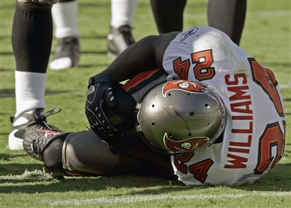Tampa Bay Buccaneers' Carnell Williams grabs his knee after being hit in the first quarter against the Carolina Panthers.